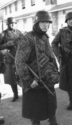 A Waffen-SS detachment. Note the MP40 submachine gun carried by the soldier in the camouflage smock.