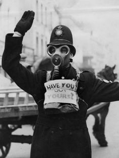A Gloucestershire traffic policeman wears a sign reminding the public to wear their gas masks. (Photo by Fox Photos/Getty Images)