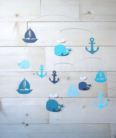 This handcrafted teal, navy and blue nautical mobile, featuring whales, sailboats and anchors, is perfectly balanced and lightweight, allowing it to freely spin and rotate, adding cheer to any room with its constant and gentle motion. Details:  Love Lou Home mobiles are balanced by hand. Each shape spins independently and the precise length of the threads and wires allow this mobile to move without restriction. The mobile is light enough to be set into motion by the slightest movement of…