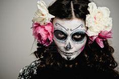 Una mujer en traje de Halloween y las flores del cráneo maquillaje celebración Foto de archivo