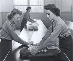 Women Marines learning how to rig parachutes at the training school at Camp Lejeune, North Carolina in 1942. From left to right: Private Marion I. Chadwick, Private Jessie O. Young, and Private Marjorie N. Barrett.