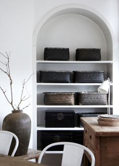 built-in arched shelving with vintage storage baskets