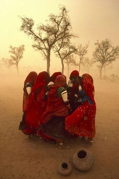 Women huddled and singing during sandstorm, Rajasthan, north-west India, June 1984. Photograph by Steve McCurry