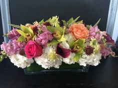 long and low centerpiece with spring/summer flowers. Designed by Juniper Flowers