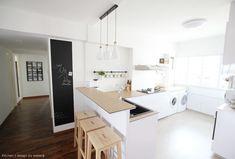カウンターテーブルとラウンドリーエリアのついた明るくオープンなキッチン