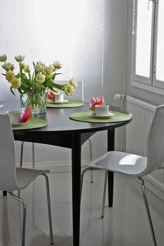 Musta pöytä ja valkoiset tuolit. Black dining table, white modern chairs.