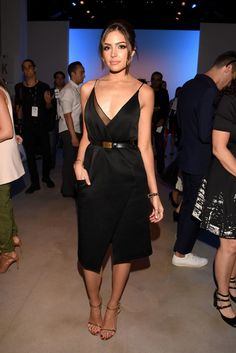 Olivia Culpo wears a black belted slip dress with metallic sandals