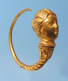 Hellenistic Greek Gold Earring  An ancient Greek gold hoop earring, embellished with a spiral coil design culminating in a finely modelled head of a woman with a melon coiffure.  Ca. 3rd-1st century BC.