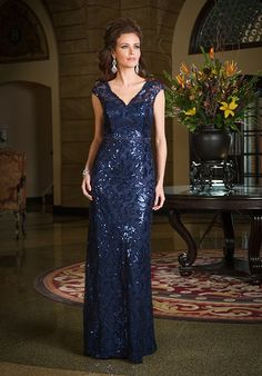Fitted A-line gown with beaded natural waistband, Floral Paillette fabric, and illusion v-front and back neckline with cap sleeves. Petite Sizing Available.
