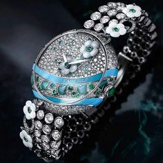 Fabergé watches Summer in Provence high jewellery timepiece features a garland of white mother-of-pearl flowers, meandering across the diamond and gem-set dial and bracelet. Limited to five pieces, the 37mm model comes in a white gold case, set with 322 diamonds, 19 Paraíba tourmalines, 15 emeralds, turquoise enamel, and green chrysoprase leaves.