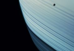 Saturn's tiny moon Mimas in transit across rippling ring shadows on the planet's northern hemisphere during that hemisphere's winter. Mimas is only 246 miles in diameter. South is up.