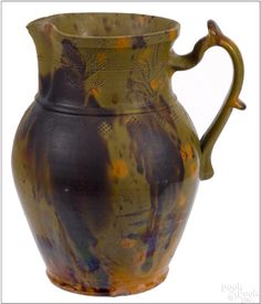 "Pook & Pook.  January 17th 2015.  Lot 286.  Estimated: $1500 - $2500.   Realized Price: $7800.   Pennsylvania redware pitcher, 19th c., with mottled green, orange, and brown glaze, the rim and body with bands of potato stamp decoration and sgraffito flowers, 11"" h."