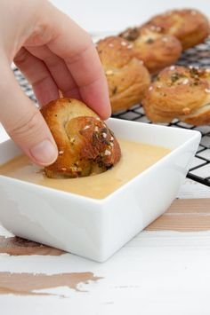 A Pretzel Garlic Knot being dipped in vegan cheese