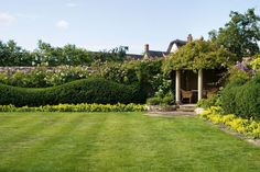 At Armscote Manor in Warwickshire, England, garden designer Dan Pearson carved a hedge into an undulating eyecatcher that adds a note of modernity to Deborah and Roy Williams's Jacobean house.