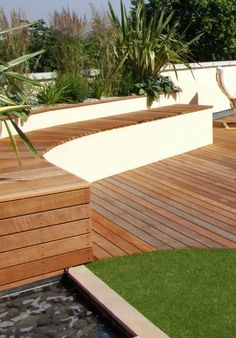 Artificial grass, hardwood decking, bench and water pool on roof garden in London