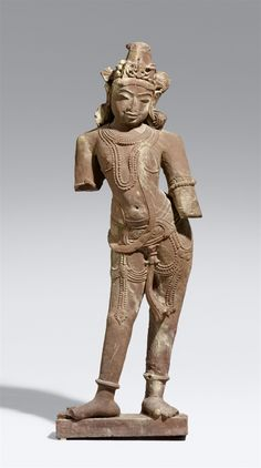 North/Central Indian pink sandstone figure of a standing male figure. 10th/12th century A North Indian pink sandstone figure of a male figure standing in tribhanga with the right foot turned out, on a small plinth, the body hung with pearl necklaces, bracelets and bangles, and various strings of pearls from the belt holding together the short dhoti, the head slighly held to the side, with large eyes and a smiling mouth, a diadem headdress and large earrings. 10th/12th century. Height 105 cm
