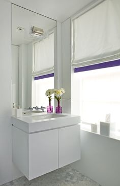 Purple shade trim is just enough color for this all white bathroom