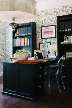 dramatic black desk + bookcases against spotted wallpapered wall