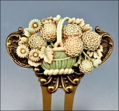 A coral flower basket rests on gold, hinged to a celluloid pin.