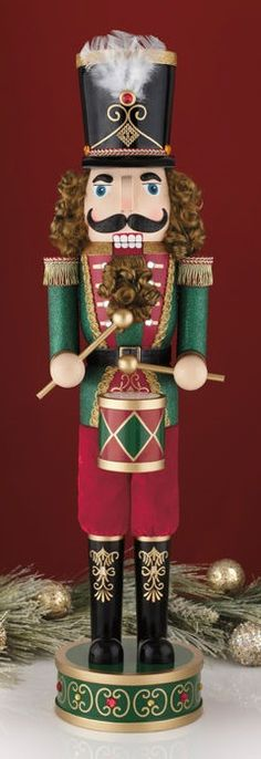 "This beautiful 32"" Drummer Nutcracker stands at the ready with his glittering green outfit and raised wooden nose, mustache and eyebrows. Dressed in his detailed band hat and drum, and standing atop a patterned base, the Drummer Nutcracker will be an exciting item for nutcracker collectors as well as a great unique piece of holiday décor."