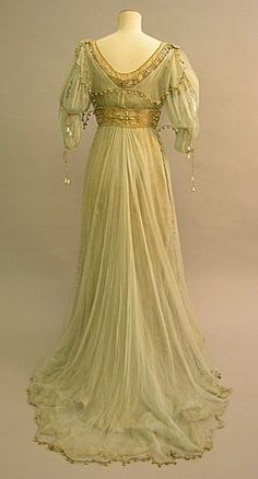 This evening dress made between 1908-1910 was worn by Maud Messel. It is made of silver gilt lame, covered with light green silk chiffon, embroidered with rosettes in pearls and glass. The dress has a long skirt with a train. The dress is worn with a green silk chiffon overdress, green silk chiffon scarves and silver braid. The design is aesthetic and medieval inspired. Its dramatic style indicates that it might have been worn as fancy dress. Back view