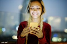 Smiling young woman using a smartphone in the evening cityscape   premium image by rawpixel.com / Teddy Rawpixel