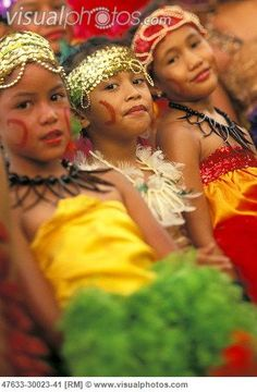 Three samoan children in colorful traditional dress with face painting.