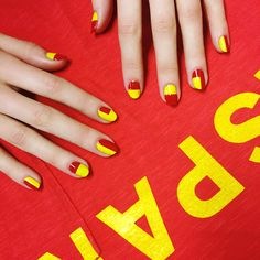 """Deeming the Spanish flag's coat of arms """"too complicated for a fingernail,"""" Poole found plenty to work with in the simple play of yellow and red. Sally Hansen All Fired Up complemented by Butter London Pimms."""