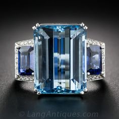 FINE AQUAMARINE, SAPPHIRE, AND DIAMOND RING. A Santa Maria aquamarine, weighing 11 carats, displaying about the finest, deeply saturated color imaginable, glistens and glows between a matched pair of rich, royal blue, emerald-cut sapphires, weighing over one carat each, framed on three sides with small sparkling white diamonds. All of these are tastefully presented in a tailored mounting, expertly and sturdily crafted in gleaming 18K white gold. A singular and sublime. Currently ring size 7.