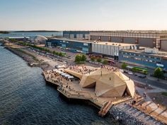 Located in a former industrial area, this undulating wooden building serves as a sauna and outdoor auditorium
