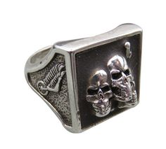 This spine tingling G&S accessory features triple grimacing skulls pushing out from a dark screen. The large base showcases intricate details including silver teeth and spiny fingers. The band has 3D wing accents on a textured canvas.