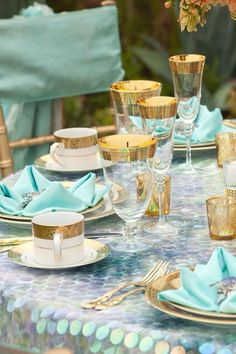 Tablescape in aqua and gold. Love the gold rimed glass from England