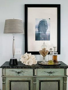 Home Decorating Tips - Art and Accessories: Working together complement a tabletop of accessories with a striking piece of wall art. Hang the art about 8 to 12 inches above the table to form an eye-pleasing connection between the items. To complete the effect, make sure that some of the accessories on the tabletop are tall enough to overlap the artwork, helping the art and accessories appear as a single unit.