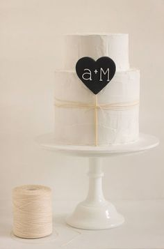 This black fondant heart with piped white letters gives this accent piece a chalkboard effect