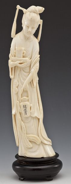 "Japanese carved ivory tusk okimono of a deity with teapot and cup. Teapot inscribed with characters. Attached to carved wood base. 19th century. MEASUREMENTS: 10"" on 1-7/8"" base"