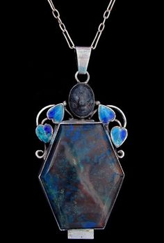 Jewellery Arts & Crafts circa 1925 - GEORGE HUNT (1892-1960) An Arts & Crafts silver pendant set with a blue swiss lapis stone surmounted by  an oval cabochon in a wirework frame with beads and enamelled leaves. English. Circa 1925.