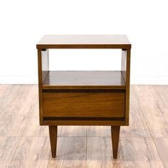 This Mid Century Modern nightstand is featured in a solid wood with a walnut finish. This vintage bedside table has a spacious single drawer, shelf, and tapered legs. Perfect in any bedroom! #midcenturymodern #dressers #nightstand #sandiegovintage #vintagefurniture