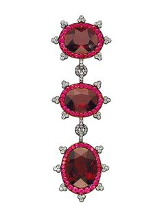 JAR brooch set with three garnets of 41.36, 33.25, and 28.42 carats circled with diamonds and rubies.