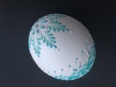 This is a goose egg pysanka painted aqua and decorated with white and aqua wax. To create this egg, I use the pinhead method also known as the drop-and-pull pinhead method. In this method, mostly used in Poland, the Czech Republic, Slovenia, and Lithuania, a pin stylus is used as a tool.