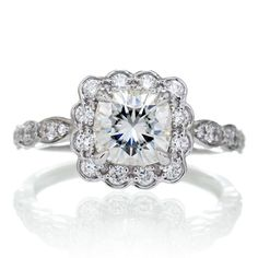 18k 1.31 carat total weight. This moissanite engagement ring features a 6x6 mm cushion forever brilliant, an ideal size, adorned with dazzling brilliant cut diamonds in a vintage style square scallop halo. A cathedral design will allow a matching wedding band to sit flush, making this moissanit