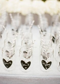 mason jar escort cards drinking glasses with chalkboard hearts (photo: lane dittoe)--actually might be worth getting enough mason jars to do this. then people woudn't (shouldn't) have to keep getting new glasses. AND green because reduces waste of plastic glasses, and people then take them home so no dishes!