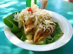 This is a dish called Vigorón. You can find it anywhere from house parties to on the street at vedors. It is made of part of a plantain tree leaf, then topped with yucca, pork, chicharrón (fried) and a cabbage and tomato salad.