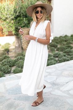 Emma Hill wears white summer midi dress, straw fedora wide brim hat, basket bag, hermes oran sandals, round ray ban sunglasses, summer outfit