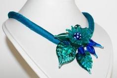 Deze ketting is gemaakt met een gevuld zijden koord in de kleur blauw/groen, de dikte van het koord is +/- 9mm. Op het koord zitten verschillende vormpjes, blaadjes, kleine kraaltjes en transparante facetkralen en tussen dit alles door zijn nog roccailles verwerkt. De lengte van het koord inclusief slotje is 45,5cm. Aan het slotje zit nog een verlengketting van 5cm. De eindkappen aan de ketting (achter in de hals) zijn ook gebrand van glas. Brooch, Jewelry, Jewlery, Bijoux, Jewerly, Jewelery, Jewels, Accessories