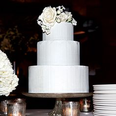 COCKTAIL PARTY WEDDING  This three-tiered, fondant-frosted confection by Bijoux Doux is classic on the outside (sugar-flower topper, check; white-on-white chevron motif, check) but mischievous on the inside (White Russian-buttercream filling, check!).