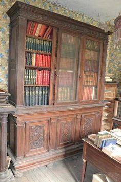 Grande bibliiothèque à portes coulissantes en partie haute et sculptée