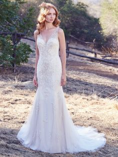 Maggie Sottero - KYRA, Vintage-inspired beading and Swarovski crystals add unique glamour to this soft fit-and-flare wedding dress, featuring a plunging V-neckline, sheer straps, and illusion keyhole back. Lined with Inessa Jersey for a luxe fit. Finished with covered buttons over zipper closure.