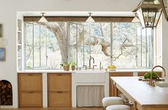 """Wanting to harness """"every bit of natural light,"""" Steve designed a wall of windows to connect inside and out and flood the room with sunshine. A farmhouse sink sits atop white-oak cabinets, a material used throughout the home for """"a sense of continuity."""""""