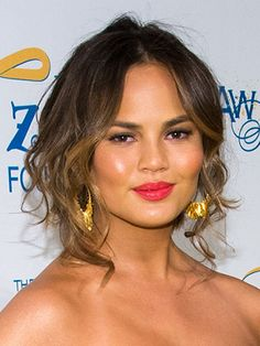 Copy Chrissy Teigen and stick to a simple updo with face-framing curls for a beach wedding.