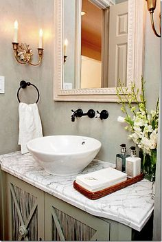 White marble counter with white vessel sink for a powder room. Faucets on the wall - not keen on the color - it fights the gold sconces and towel ring is intrusive. I think they should have gone with antique pewter/nickel. Sconces on wall. Lovely mirror.